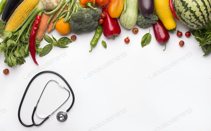 Stethoscope and organic vegetables isolated on white