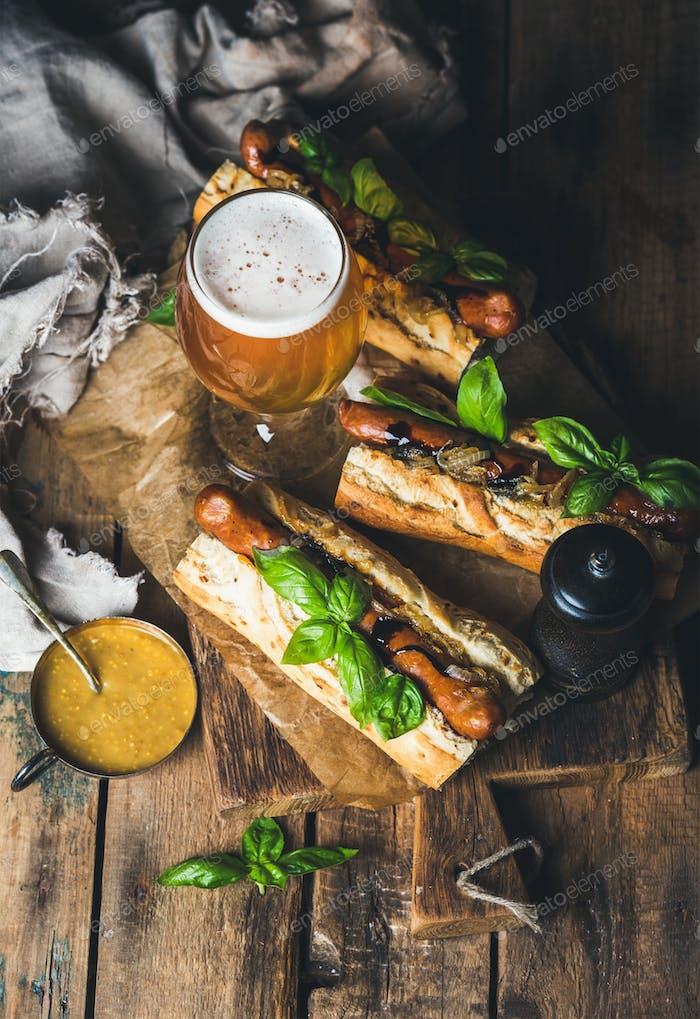 Glas ungefiltertes Bier und gegrillte Wursthunde im Baguette
