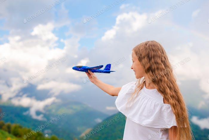 Happy little girl with toy airplane in hands in mountains