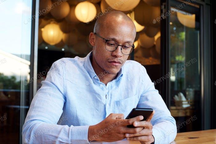afrikanische Geschäftsmann sitzen mit Handy