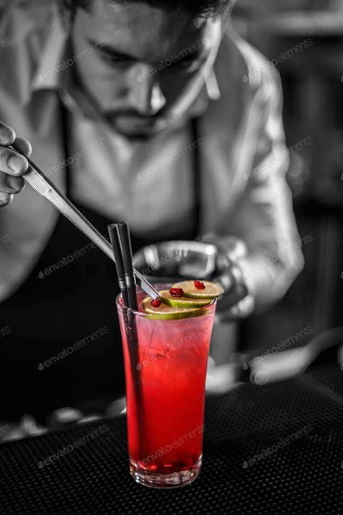 Bartender decorating non-alcoholic pomegranate cocktail