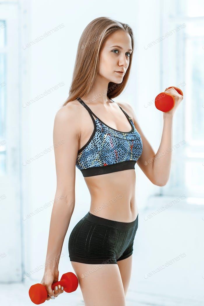 Sportliche Frau tun Aerobic-Übung mit roten Hanteln