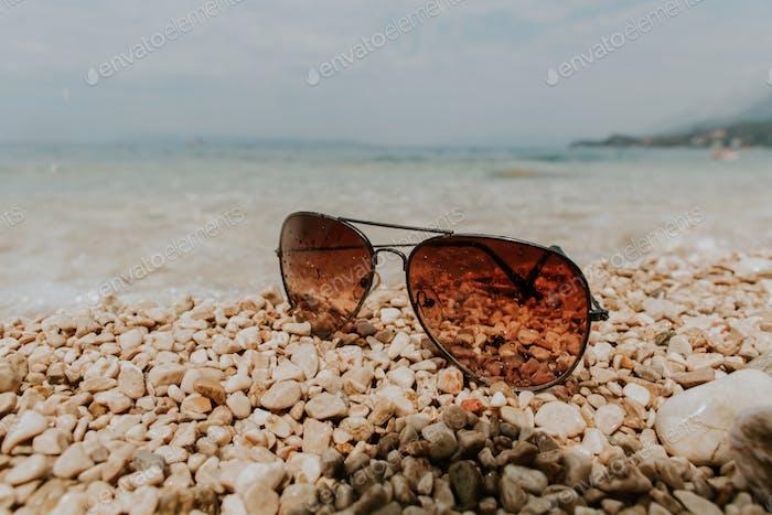 Sunglasses on beach in summer.