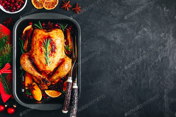 Christmas baked chicken or turkey with spices, oranges and cranberries