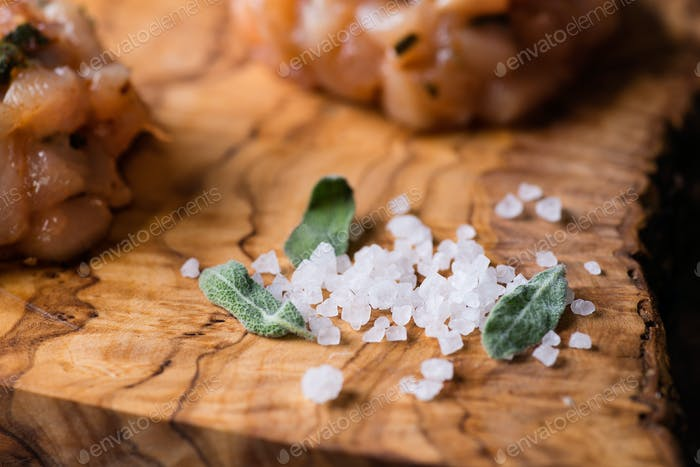 Sea salt with fresh sage on olive wood board