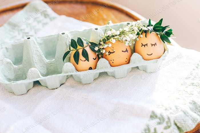 Stylish Easter eggs with cute faces in floral wreath crowns in carton tray