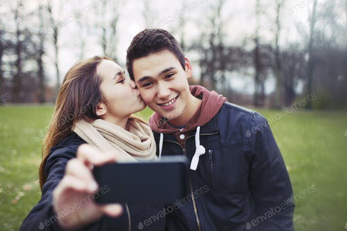 Loving teenage couple taking self portrait with a mobile phone
