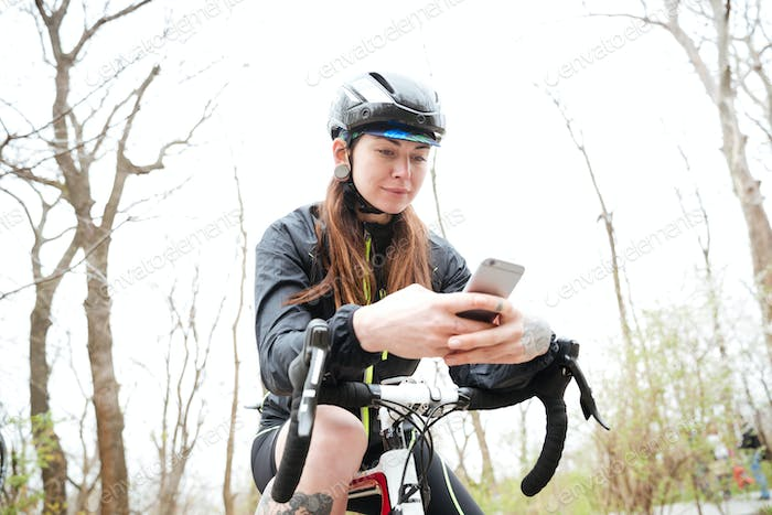 Woman on bycicle using smartphone