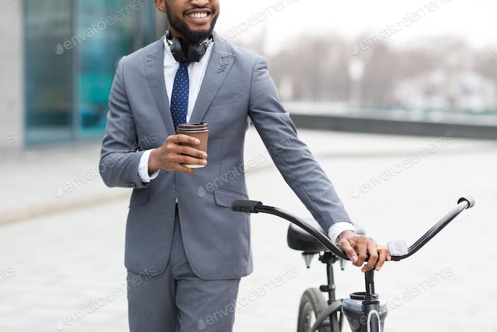 Businessman coming to work by bike and drinking coffee outdoors