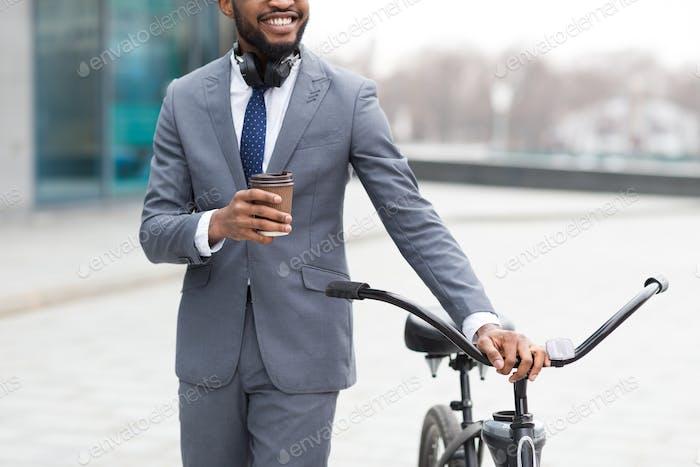 Geschäftsmann kommt mit dem Fahrrad zur Arbeit und trinken Kaffee im Freien