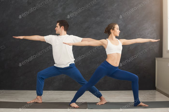 Young couple practicing yoga together in gym