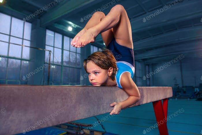 beautiful girl is engaged in sports gymnastics on a log