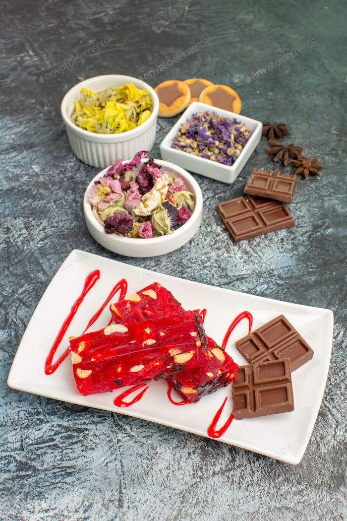 a plate of chocolate with bowls of dry flowers and cookie and chocolate bars on grey ground