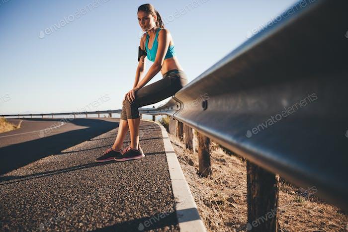 Young female runner taking a break