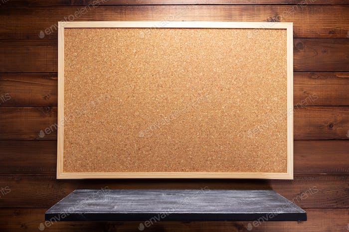 Korkplatte und Regal auf Holzhintergrund