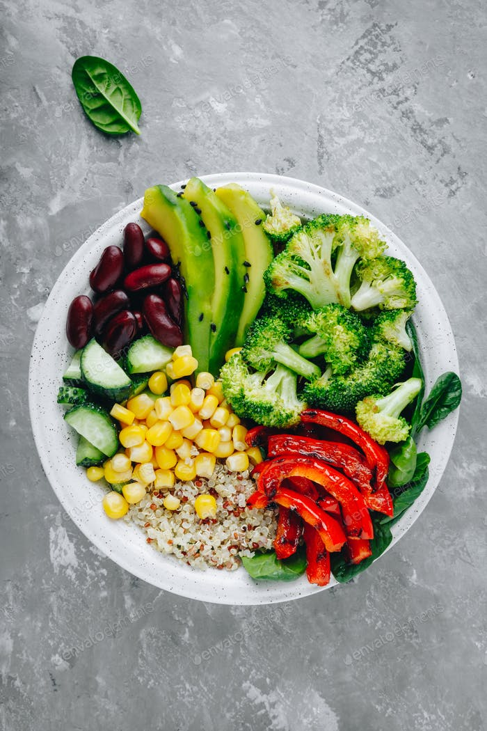 Healthy bowl salad quinoa, spinach, avocado, beans, sweet corn, broccoli, cucumbers and paprika