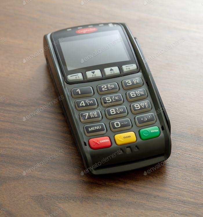Zahlungsautomat, POS-Terminal auf Holzhintergrund.