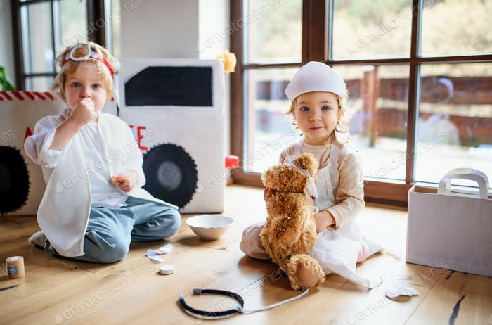 Two small children with doctor uniforms indoors at home, playing