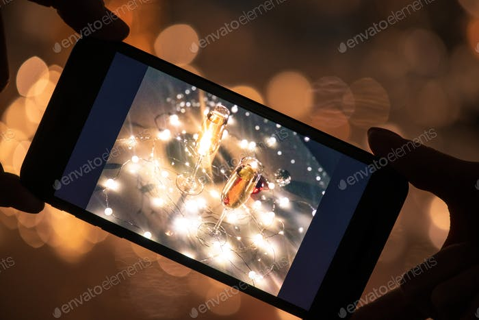 Human hands holding smartphone with image of two flutes of champagne on table