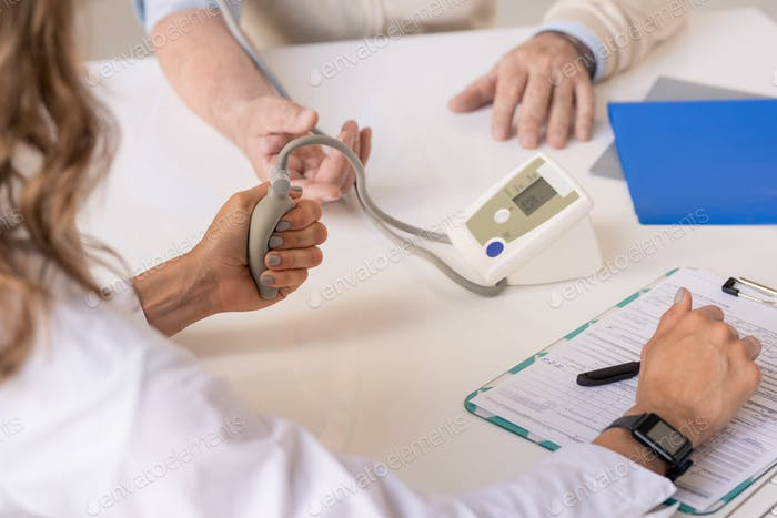 Hands of therapeutist pressing tonometer pump while measuring blood pressure