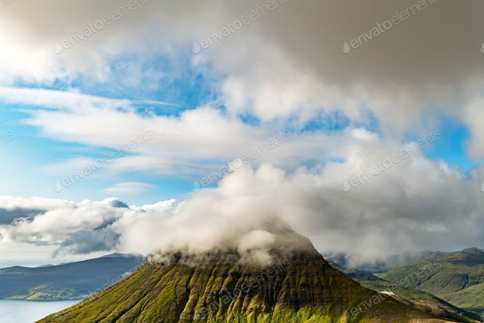Foggy mountain peaks and clouds covering sea and mountains