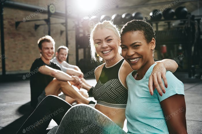 Two laughing women sitting in a gym after working out