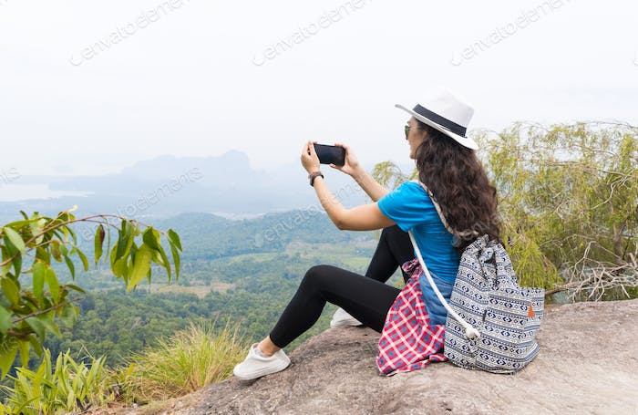 Woman With Backpack Take Photo Of Landscape From Mountain Top On Cell Smart Phone Back Rear View