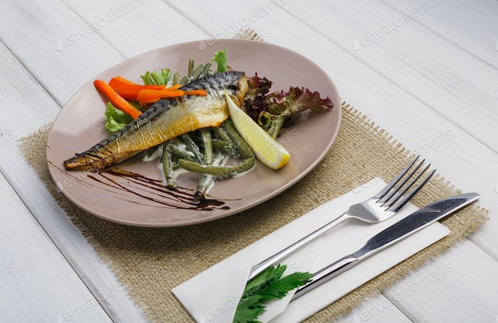 Restaurant food on wooden table. Smoked mackerel with vegetables closeup