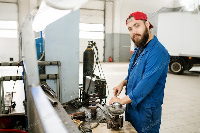 Young bearded repairman using wrench or other handtool to fix parts of engine