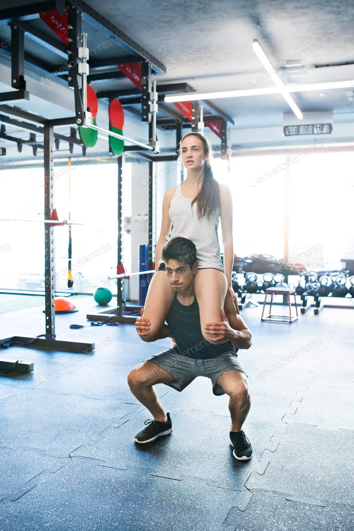 Man carrying woman on his shoulders, doing squats.