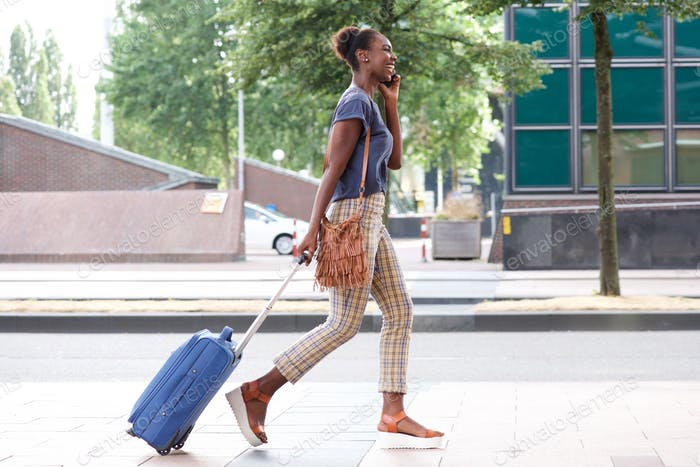 Side portrait of happy african american woman walking in city with mobile phone and suitcase