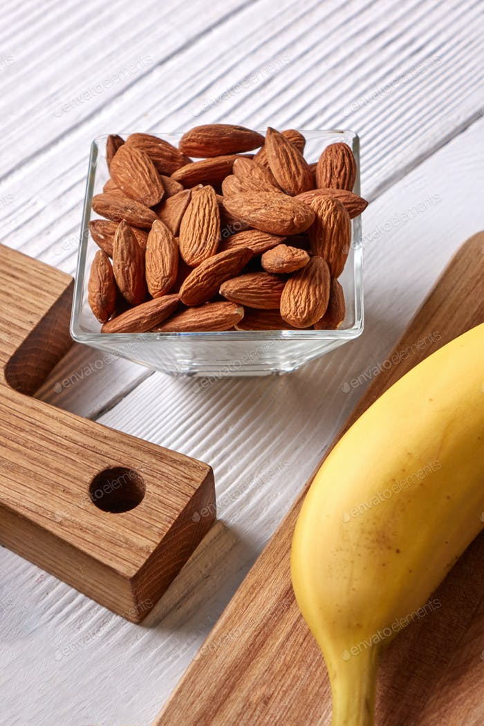 Natural ingredients for healthy breakfast- almonds in a glass bowl and fresh banana on a wooden