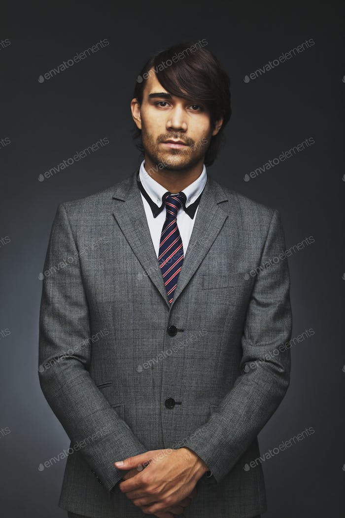 Handsome young businessman looking at camera