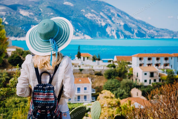 Tourist woman with blue sunhat and travel backpack admire view of colorful tranquil village Assos on