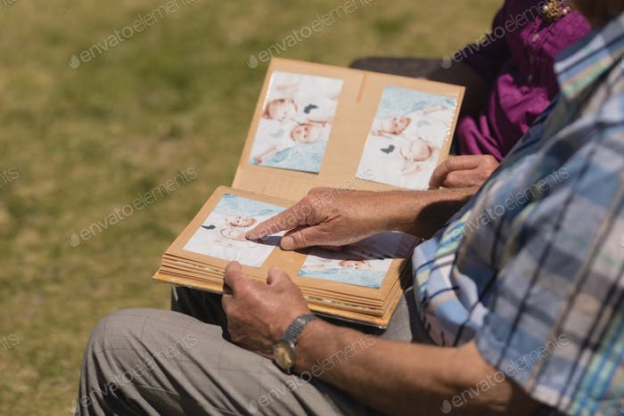 Mid section of senior couple looking at photo album and the man showing a photo in the park