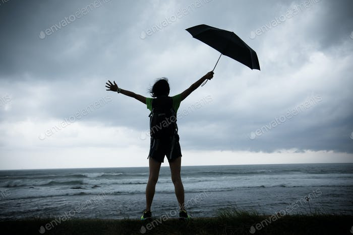woman with umbrella in the storm seaside