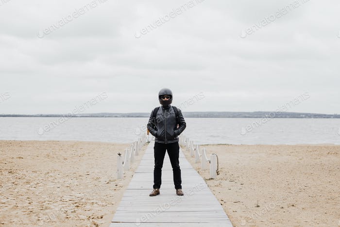 Man Standing on Beach and Facing Water
