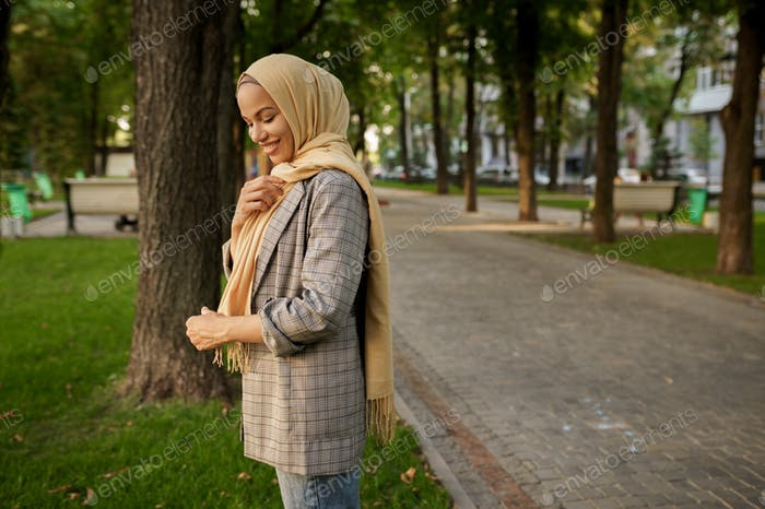 Attractive arab girl in hijab poses in summer park