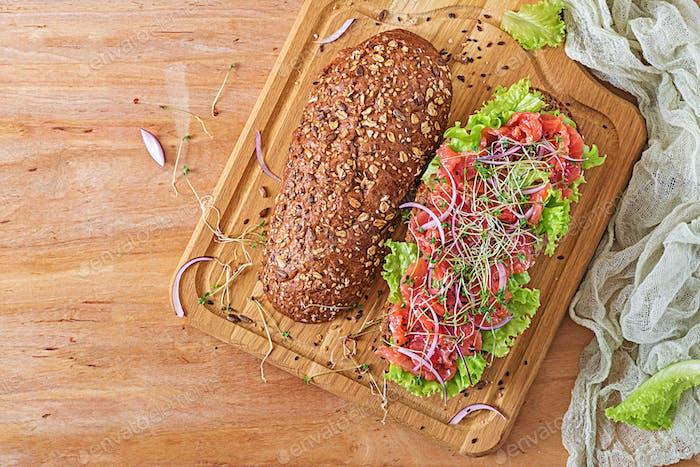 Lachs-Sandwich - smorrebrod mit Käsecreme und Mikrogrün auf Holztisch. Ansicht von oben