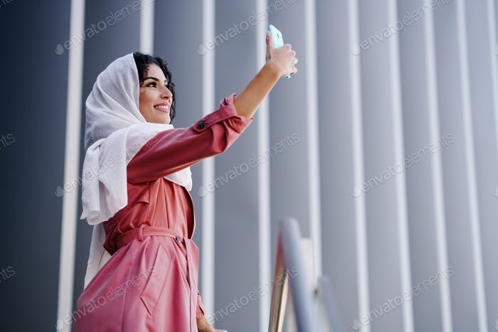 Muslim Woman with hijab taking selfie with smartphone