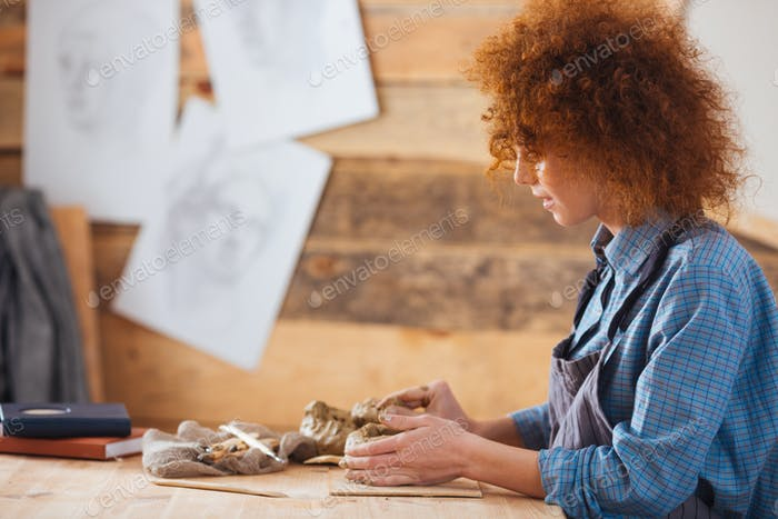 Focused woman ceramist creating sculpture using clay in pottery workshop