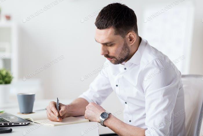 businessman writing to notebook at office
