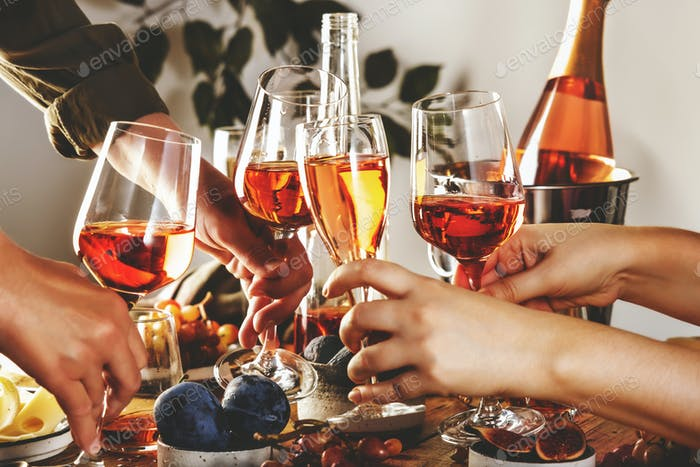 Hands holding glasses with rose wine over the table served for festive dinner party