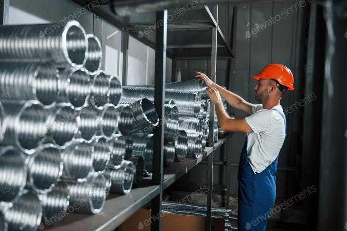 Man in uniform works on the production. Industrial modern technology