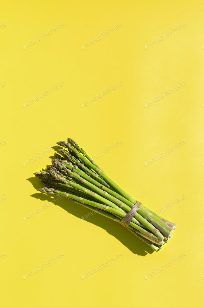 Asparagus with trendy hard light and shadows yellow background