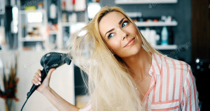 Smiling young woman blow drying hair