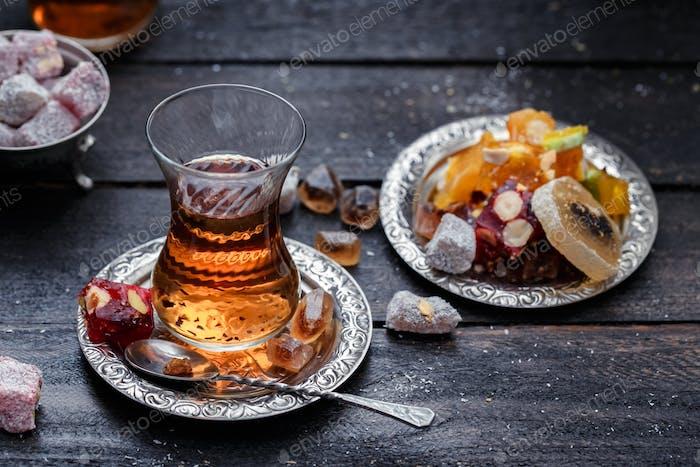 Un vaso de té tradicional brillante con Fondo Oscuro y borroso.