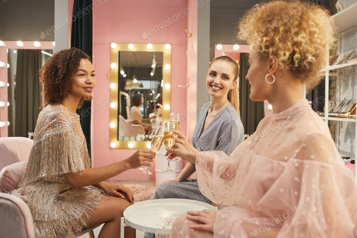 Young Women Drinking Champagne in Clothing Boutique