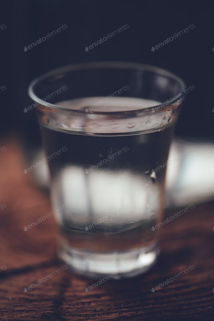 Strong alcohol drink in bottle with shot glass
