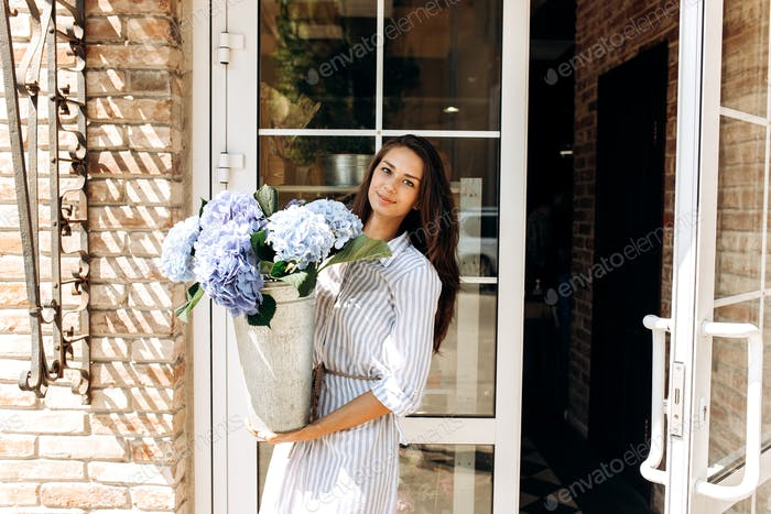 Beautiful brunette girl dressed in a striped dress smiles and and hold a vase with light blue